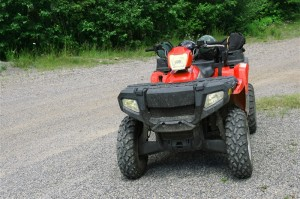 ATV (All Terrain Vehicle) on path in the midst of a forest.